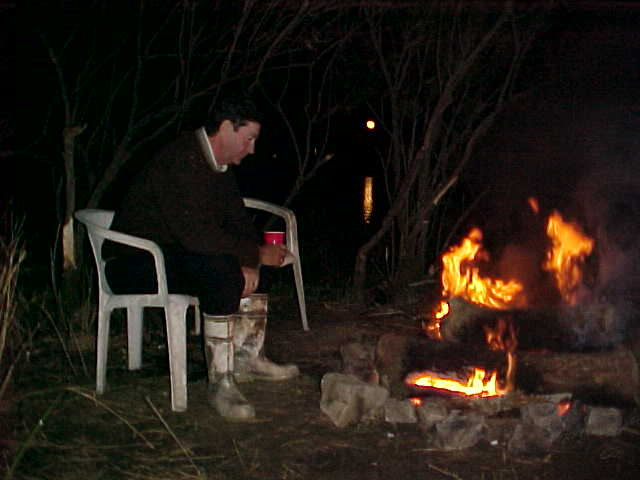 Joe enjoying the warmth of the fire and a toddie as the moon rises over the marsh.