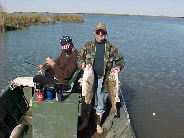 Anchored at the intersection of two canals and the lake, Dick shows off 2 nice reds. (Notice two other reds laying in the bottom of the boat.)