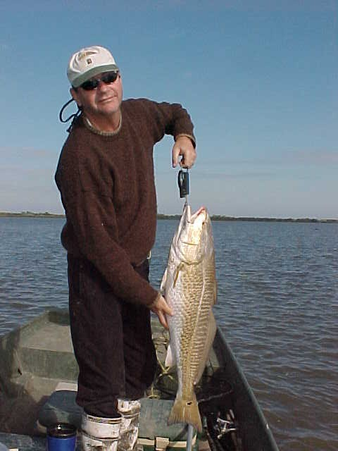 Joe shows off his beautiful 22 lb. redfish caught on the shore of the lake.