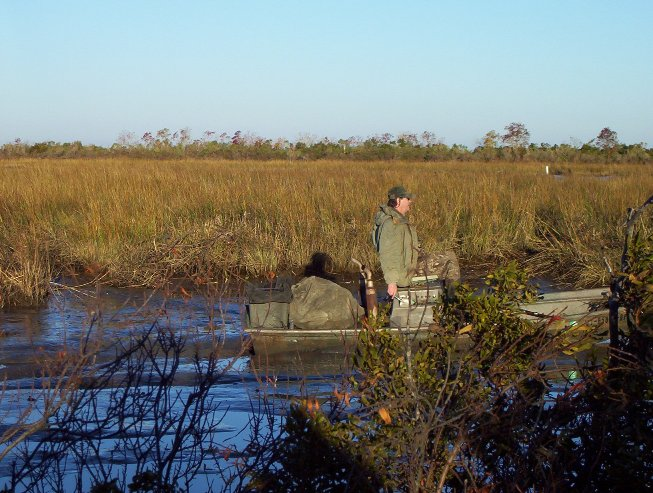 Joe trudging the mud boat through the pond after retrieving the ducks.